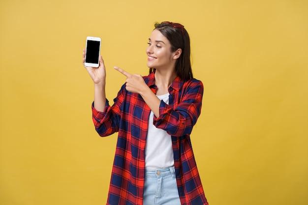 Ritratto di una giovane ragazza felice vestita in estate che punta il dito a schermo vuoto