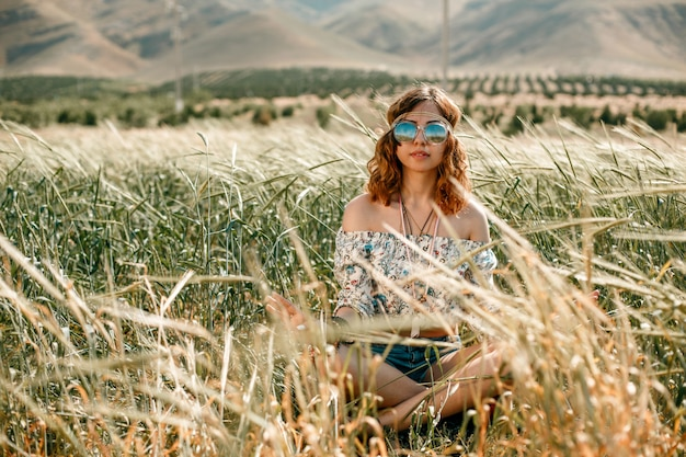 Ritratto di una giovane ragazza hippie su un campo di grano