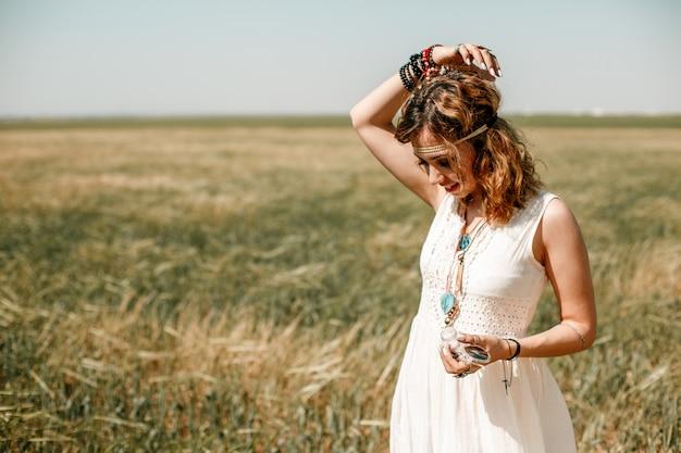 Ritratto di una giovane ragazza in un abito bianco traslucido in stile boho o hippie