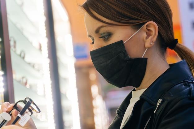 Ritratto di una giovane ragazza in una mascherina medica che sceglie gli occhiali