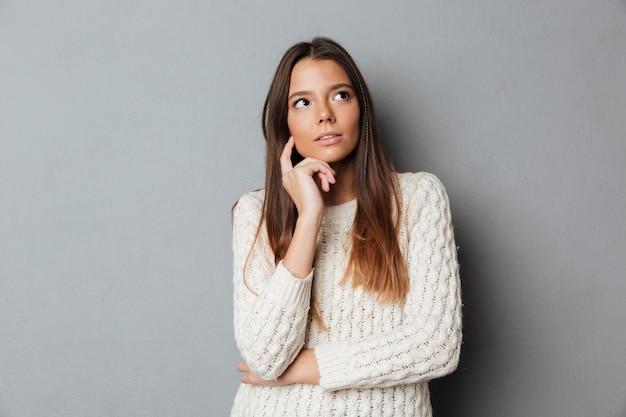Ritratto di una giovane ragazza premurosa in maglione