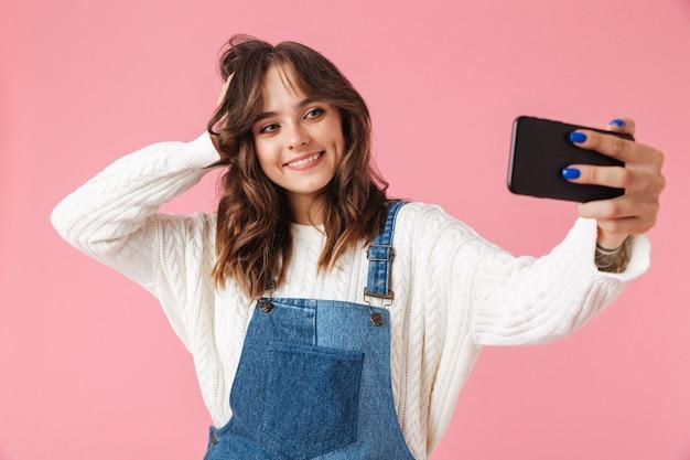 Ritratto di una giovane ragazza sorridente che cattura un selfie