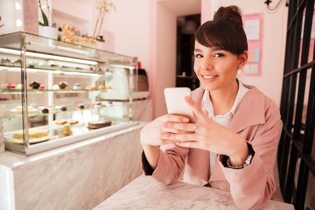 Ritratto di una giovane ragazza sorridente messaggio sms