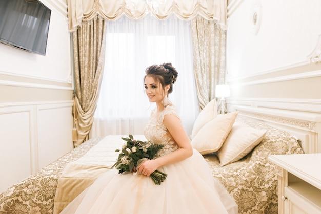 Ritratto di una giovane sposa attraente con un bouquet invernale. sposa del mattino in un hotel di lusso
