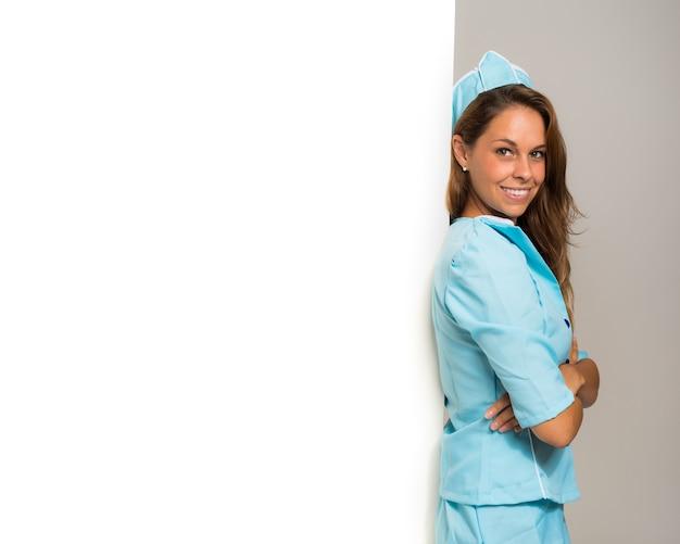 Ritratto di una hostess sorridente che mostra un pannello vuoto