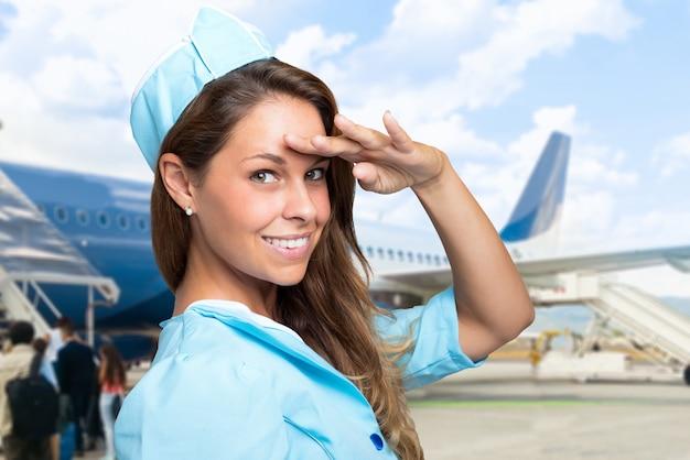 Ritratto di una hostess sorridente di fronte a un aereo