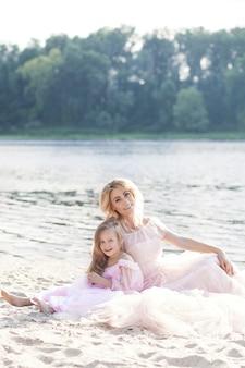Ritratto di una madre bionda e sua figlia in bellissimi abiti sulla sabbia con un lago sullo sfondo. famiglia felice che gode di una giornata di sole sulla spiaggia. stile di vita familiare, concetto di amore familiare.