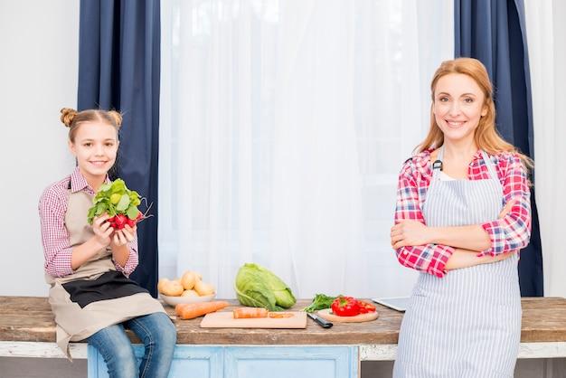 Ritratto di una madre e una figlia sorridenti davanti a verdura