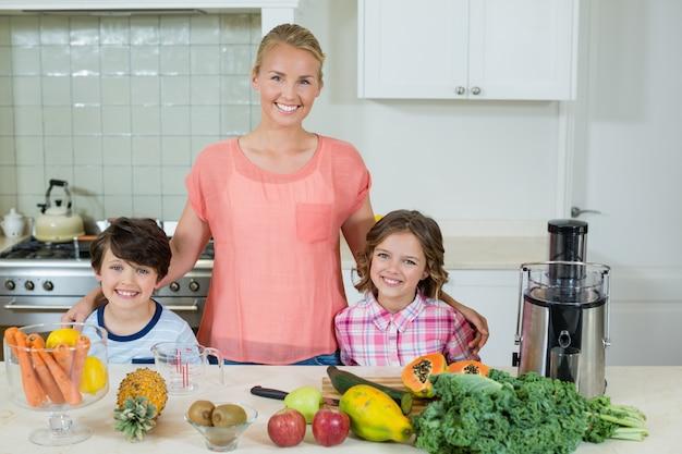 Ritratto di una madre felice e dei suoi due bambini in piedi in cucina