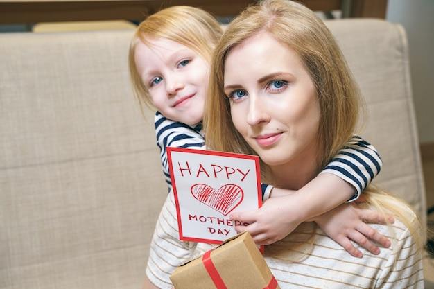 Ritratto di una madre felice e una figlia che abbraccia e che tiene una carta e un regalo a casa. la festa della mamma concetto.