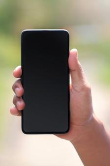 Ritratto di una mano che tiene uno smartphone. smartphone per la progettazione di mockup