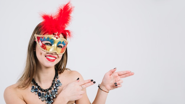 Ritratto di una maschera d'uso sorridente di carnevale della donna che gesturing sul fondo bianco