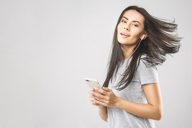 Ritratto di una musica d'ascolto della donna sveglia allegra in cuffie e nel ballare isolato su un fondo bianco. usando il telefono.