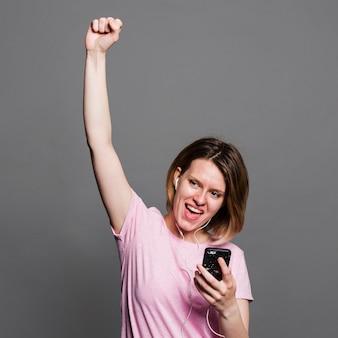 Ritratto di una musica d'ascolto della giovane donna sui trasduttori auricolari tramite il telefono cellulare contro la parete grigia