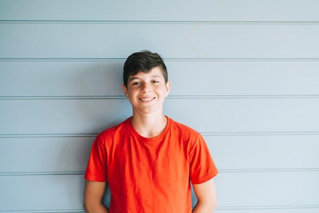 Ritratto di una parete di legno appoggiantesi teenager maschio allegra mentre guardando macchina fotografica