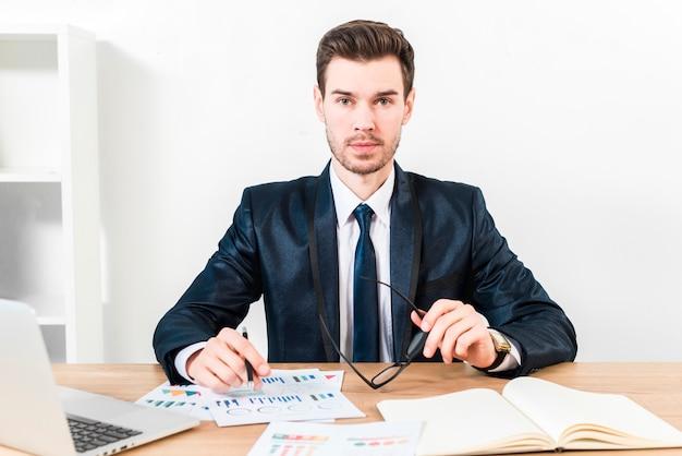 Ritratto di una penna di tenuta del giovane uomo d'affari sopra il grafico e gli occhiali a disposizione che guardano alla macchina fotografica