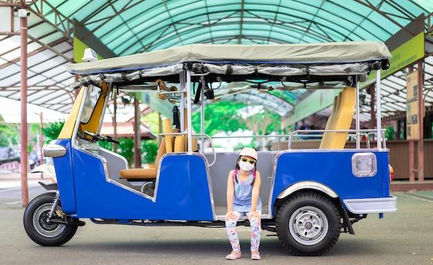 Ritratto di una piccola ragazza asiatica che indossa maschera e cappello seduto in tuk tuk taxi
