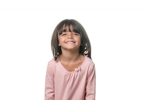 Ritratto di una piccola ragazza bruna in posa isolato su sfondo bianco.