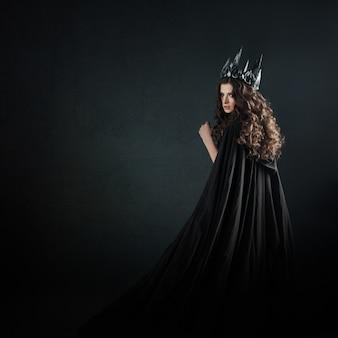 Ritratto di una principessa gotica. bella giovane donna bruna in corona di metallo e mantello nero.