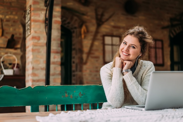 Ritratto di una ragazza adorabile con le cuffie e il computer portatile al cottage della campagna.