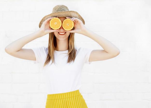 Ritratto di una ragazza allegra che tiene due fette di un'arancia al suo fronte sopra la parete bianca