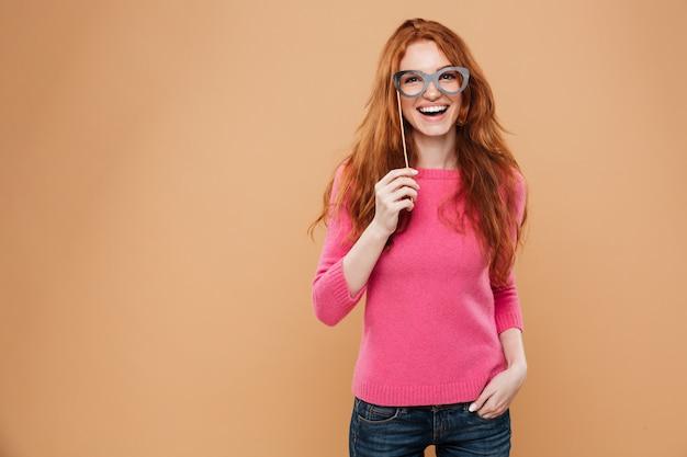 Ritratto di una ragazza allegra giovane rossa con gli occhiali da festa
