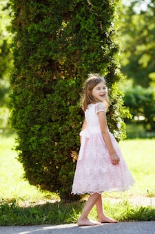 Ritratto di una ragazza allegra in un lussureggiante abito rosa nel parco.