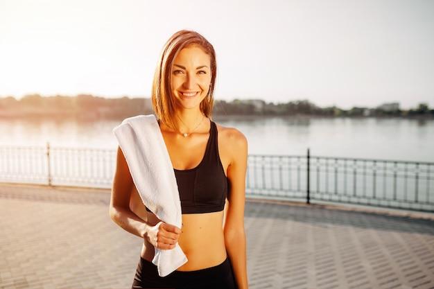 Ritratto di una ragazza atletica. bello giovane modello di forma fisica di sport che si prepara per fare jogging nel parco della città.