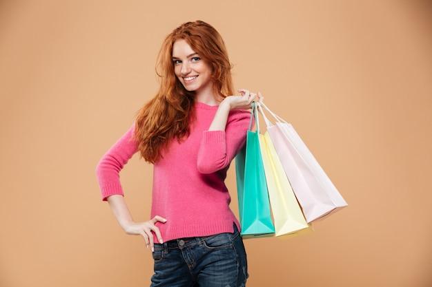 Ritratto di una ragazza attraente felice rossa con borse della spesa