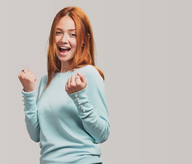 Ritratto di una ragazza bella rossa festeggia qualcosa