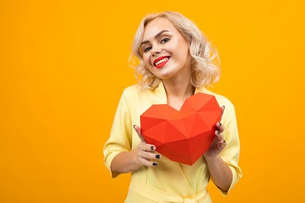 Ritratto di una ragazza bionda con il trucco con un cuore 3-d dalla carta su un giallo