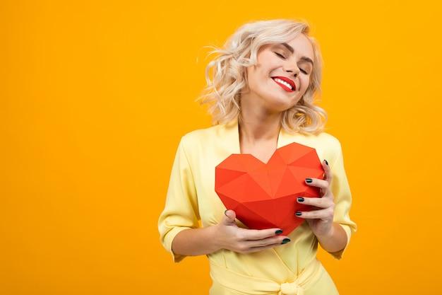 Ritratto di una ragazza bionda felice con trucco con cuore 3d fatto di carta su giallo