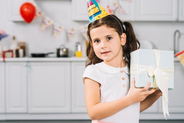 Ritratto di una ragazza carina che tiene il regalo di compleanno in cucina