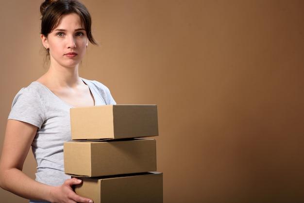 Ritratto di una ragazza carina con i capelli raccolti con scatole di cartone in mano su uno spazio beige. scatola del prodotto