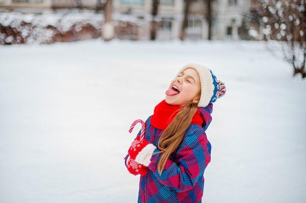 Ritratto di una ragazza carina con lecca-lecca di natale nelle mani su una strada d'inverno.