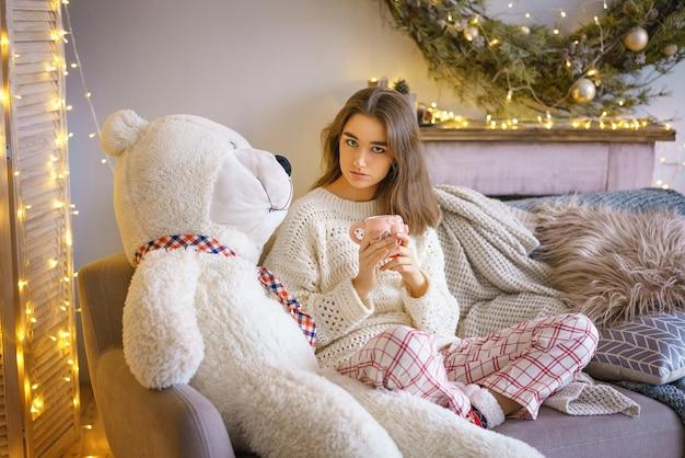 Ritratto di una ragazza carina con un orso di peluche e ghirlande con bokeh