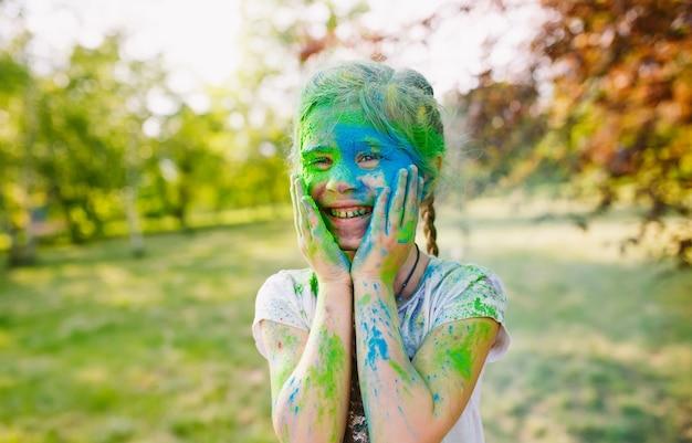 Ritratto di una ragazza carina dipinta nei colori del festival di holi.