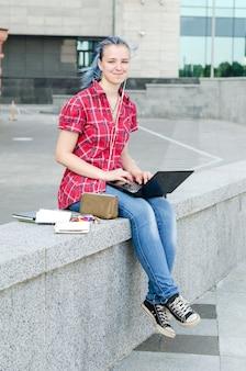 Ritratto di una ragazza carina e giovane casual con i capelli blu, lavorando sul suo computer portatile in città in una calda giornata estiva