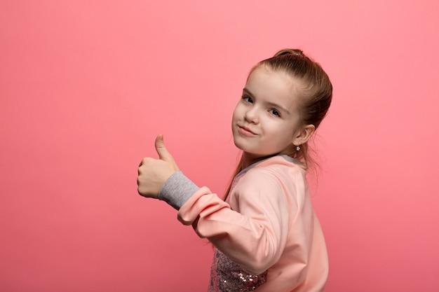 Ritratto di una ragazza caucasica in studio su uno sfondo rosa isolato che mostra i gesti con le mani
