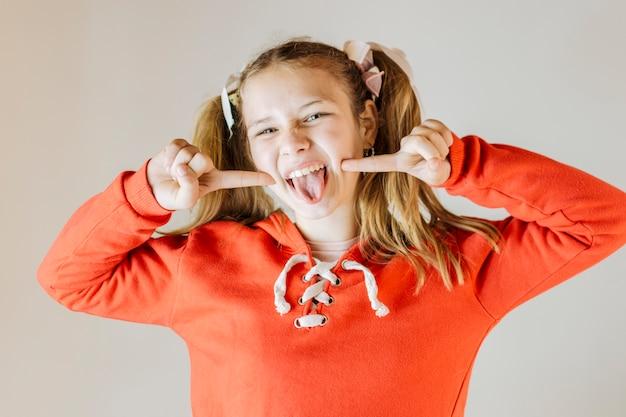 Ritratto di una ragazza che attacca fuori la lingua