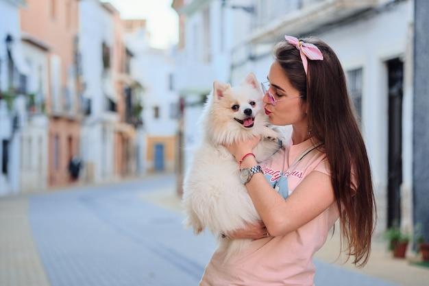 Ritratto di una ragazza che bacia il suo cane pomeranian lanuginoso bianco.