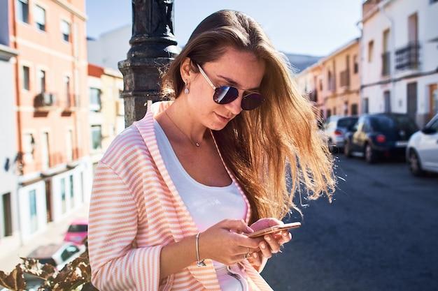 Ritratto di una ragazza che cammina e che scrive i messaggi su un telefono cellulare nella via