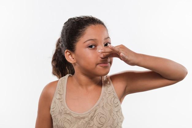Ritratto di una ragazza che copre il naso a causa del cattivo odore