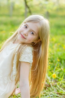 Ritratto di una ragazza che è seduta sull'erba