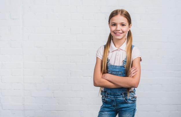 Ritratto di una ragazza che guarda alla macchina fotografica che sta contro il muro di mattoni bianco