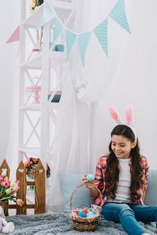 Ritratto di una ragazza che guarda le uova di pasqua seduto sul letto decorativo