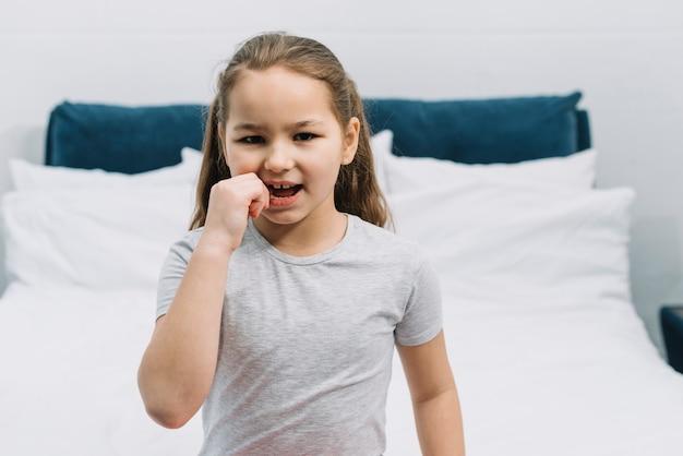Ritratto di una ragazza che ha mal di denti che tocca il suo dente