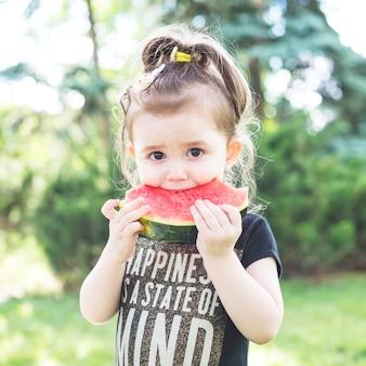 Ritratto di una ragazza che mangia la fetta di anguria fresca