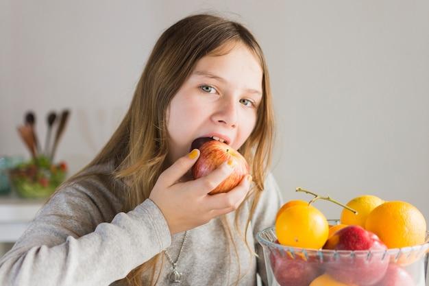 Ritratto di una ragazza che mangia mela rossa