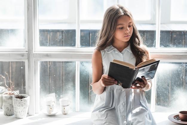 Ritratto di una ragazza che si siede davanti al libro di lettura della finestra
